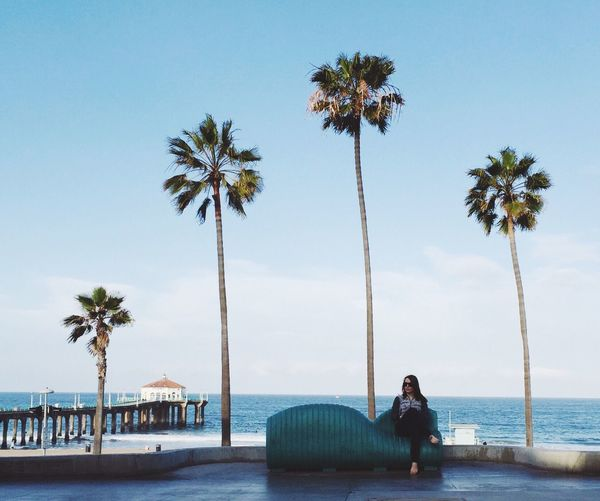 Woman resting on seat at promenade against sky