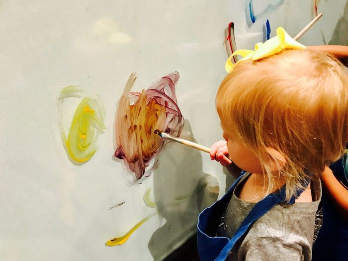 Side view of girl painting on canvas