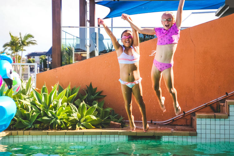 friendship and fun summer in the pool, childhood, girls, play, jumping in unison Real People Leisure Activity Front View Happiness Full Length Lifestyles Smiling Pool Looking At Camera Nature Day Enjoyment People Child Swimming Pool Portrait Positive Emotion Outdoors Girls Jumping Poolside Summertime Diversity Vacations