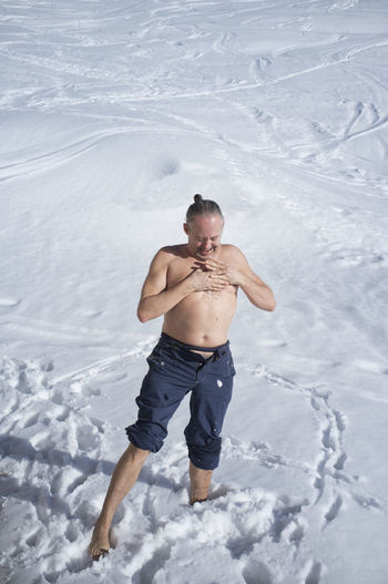 High angle view of shirtless man on snow covered land