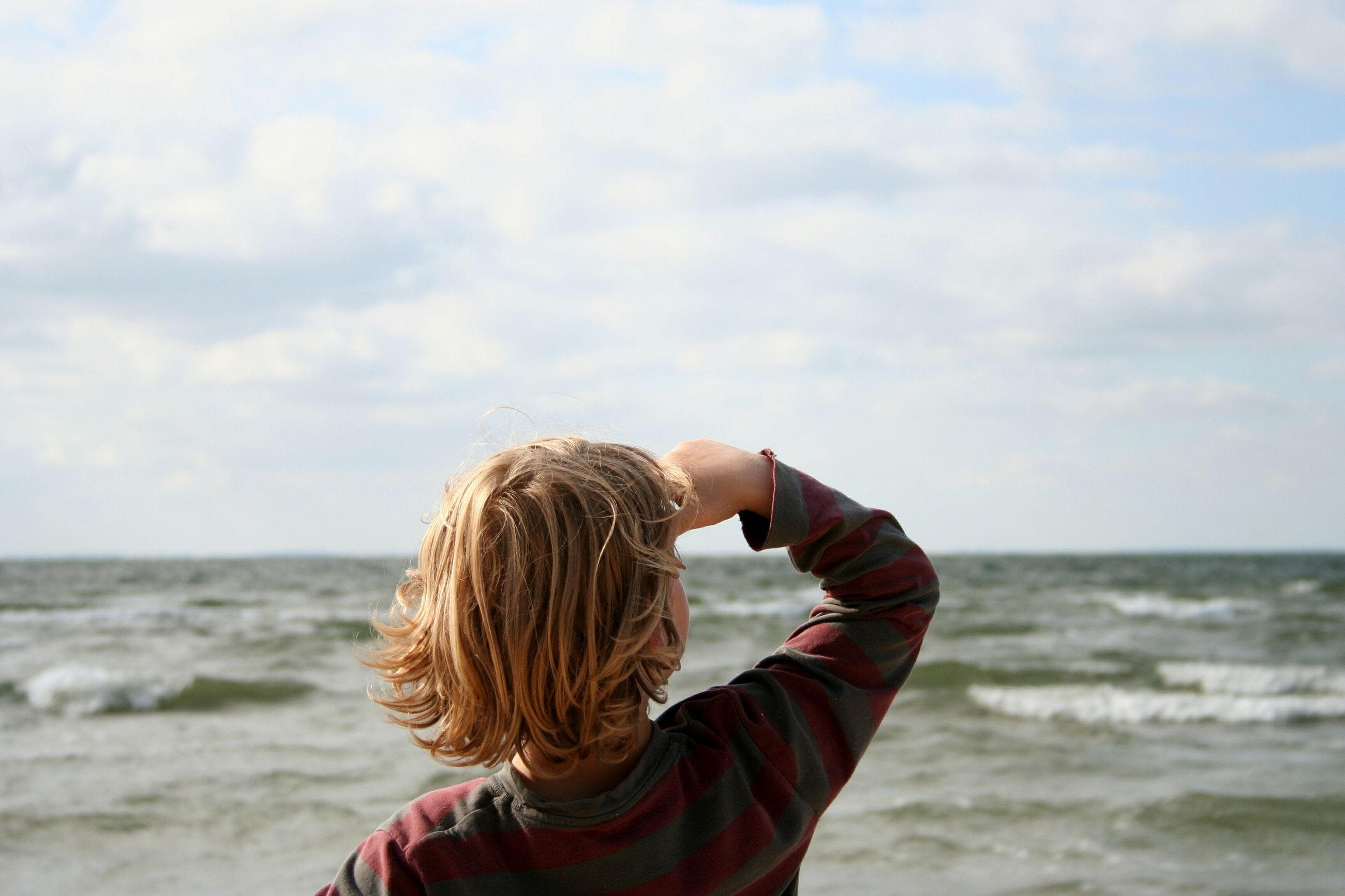 sea, leisure activity, horizon over water, lifestyles, rear view, sky, water, headshot, cloud - sky, holding, beauty in nature, non-urban scene, scenics, wave, tranquility, enjoyment, nature, tourism, casual clothing, focus on foreground, tranquil scene, travel destinations, vacations, long hair, wind, person, day