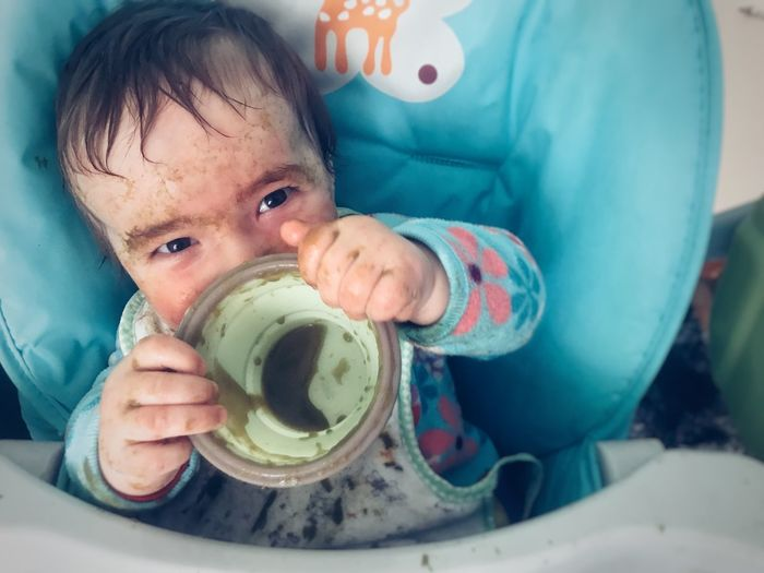 Close-up of messy baby with empty bowl