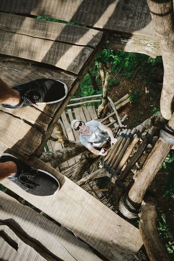 Exploring Jogja's surroundings Pine Forest Climbing Wooden Platform Man Smiling Sunglasses From My Point Of View Black Shoes Grey T-shirt Looking Down Feet Wood Wooden Planks Forest INDONESIA Java Traveling Adventure My Year My View The Architect - 2017 EyeEm Awards Out Of The Box Connected By Travel An Eye For Travel
