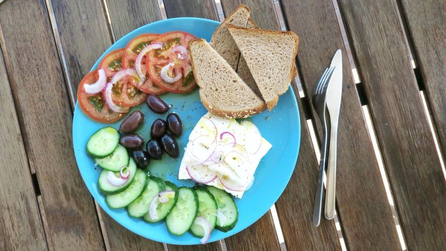 blue plate with typical greece mezze Ready-to-eat Food Greece Typical Traditional Feta Cheese Cucumber Tomato Appetizer Bread Olives Onions Bread Plate High Angle View SLICE Variation Starter Salad Greek Food Sliced Bread Served