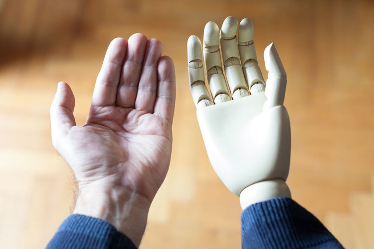 Cropped Image Of Man By Robot Hand