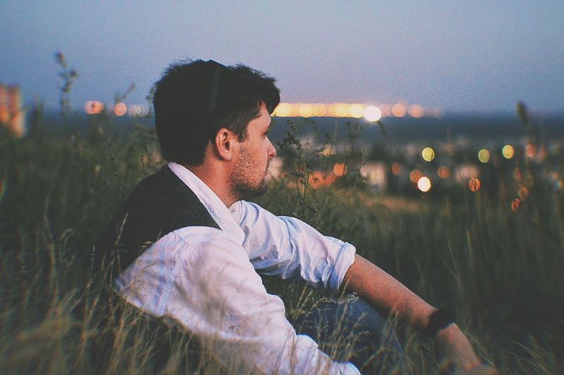 Side view of young man looking away while sitting on field against sky during sunset