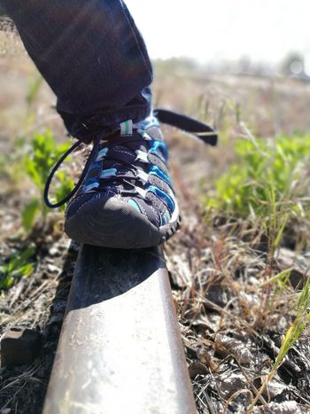 Focus On Foreground Day Outdoors No People Close-up Grass Rail Train LINE Weedy Young Adult Out Of Order Standing Summer Low Section Human Body Part Cropped Body The Purist (no Edit, No Filter) Shoe Hiking Sandal Childhood The Great Outdoors - 2017 EyeEm Awards Out Of The Box Let's Go. Together. Your Ticket To Europe