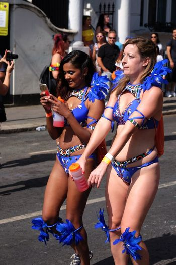 Multicultural Carnival Composition Dancing Fun GB Happy London Tourist Attraction  Blue Colour Capital City Carnival Costumes Cheerful Communication Dancers Full Frame Incidental People Leisure Activity Mobile Phone Nottinghill Carnival Real People Smiling Togetherness Travel Destination Two Dancers Uk Young Women