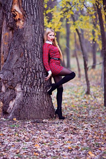Full length of seductive woman leaning on tree in forest