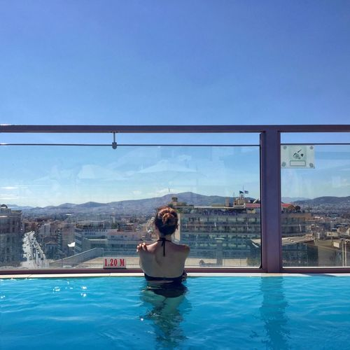 Rear view of woman in swimming pool looking at city against clear blue sky