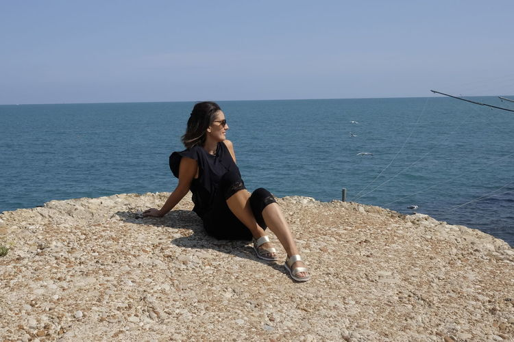 Young woman sitting on rock at beach against clear sky