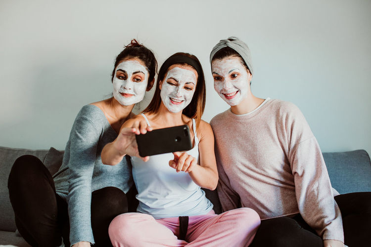Cheerful female friends with facial masks taking selfie against wall at home