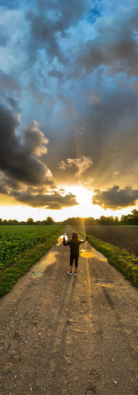 Rear view of woman with dog on road against sky during sunset
