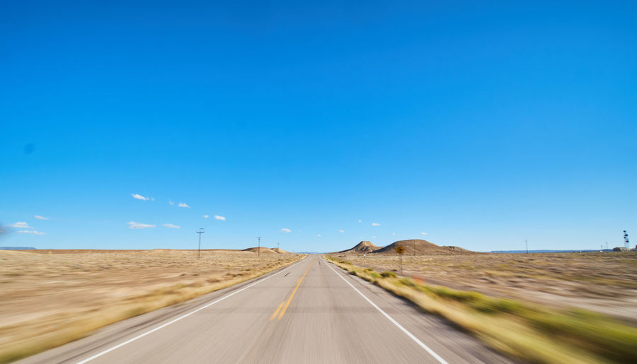 Sky Direction The Way Forward Transportation Road Blue Diminishing Perspective Nature Symbol Sign Environment vanishing point Landscape Road Marking Copy Space Marking No People Clear Sky Day Empty Road Outdoors Dividing Line
