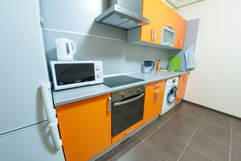 Indoors  Architecture Building No People Flooring Furniture Appliance Home Kitchen Orange Color Tile Modern Domestic Kitchen Wall - Building Feature Built Structure Cabinet Domestic Room Drawer Household Equipment Home Interior Tiled Floor