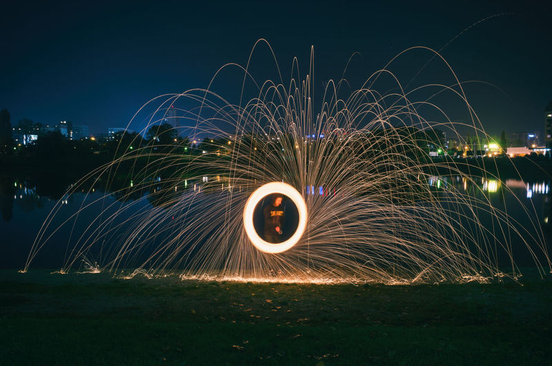 Man seen through wire wool against sky at night