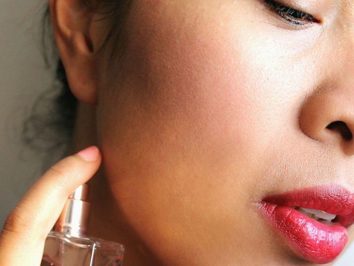 Cropped image of beautiful woman applying perfume