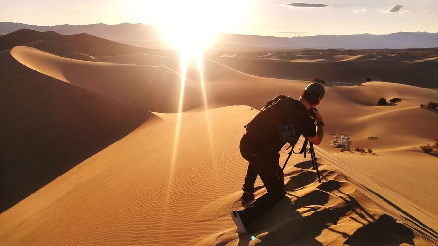 Photographer photographing shining sun over desert