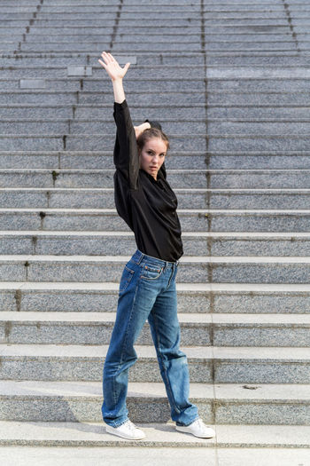 Full length portrait of a casually dressed young woman with arm raised One Person Casual Clothing Jeans Staircase Caucasian Young Woman Young Adult Outdoors Outside Natural Lighting Full Length Arm Raised Front View Arms Raised Real People Looking At Camera Steps And Staircases Human Limb Day Human Arm Beautiful Woman Jeans