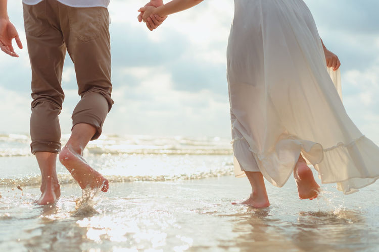 Low section of couple walking on sea shore