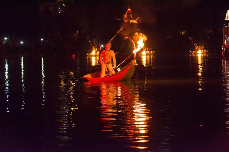 Man on illuminated boat in river at night