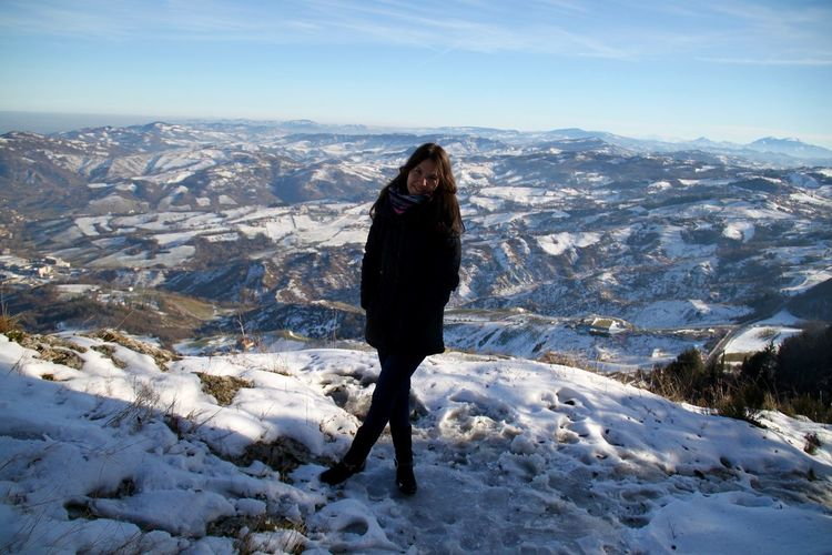 Portrait of woman standing on cliff during winter