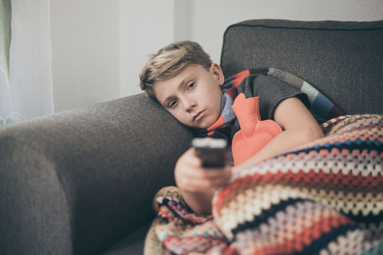Portrait of boy lying on sofa at home