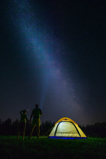 People Standing By Tent On Field Against Sky At Night