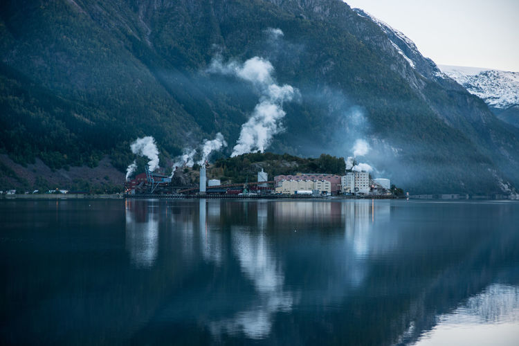 Factory by lake and mountain