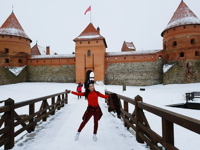 Full length of woman standing by railing against castle during winter