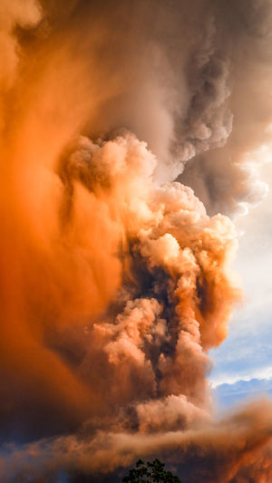 Low angle view of smoke against sky at sunset
