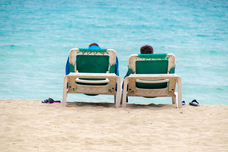 Rear view of people sitting on chair at beach