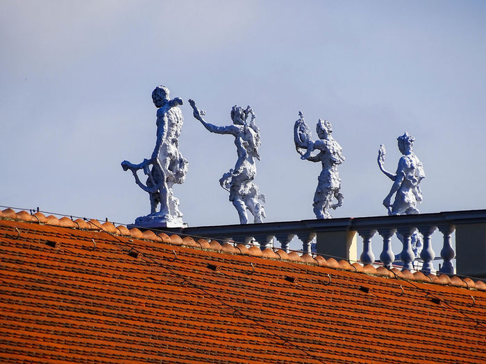 Low angle view of sculpture on roof against sky