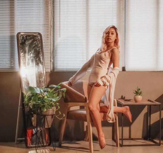 Sensual woman by chair looking away at home