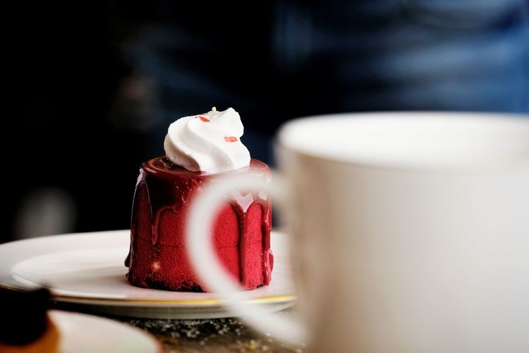 Close-up of red cake in plate on table