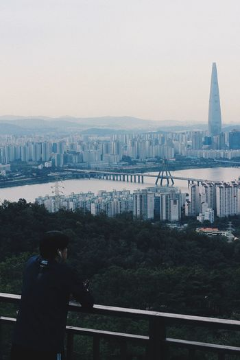 Man standing on bridge over river in city