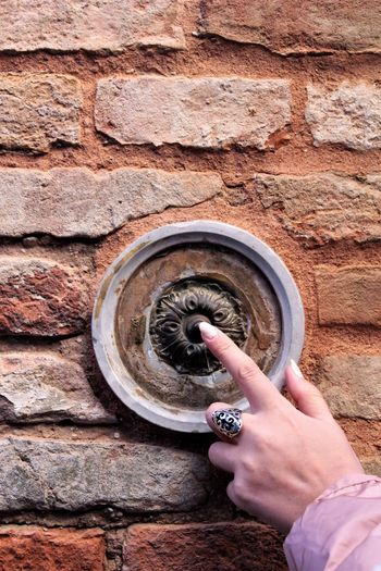 Venice and its beautiful bell buttons. Round Round Shape Textures and Surfaces Texture Tactile Ring Brick Brick Wall Button Bell Bell Button Index Finger Red Orange Color Venice Italy Human Hand Holding Human Finger Close-up Rock - Object