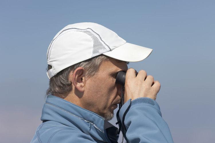 Side view of man looking through binoculars against clear sky