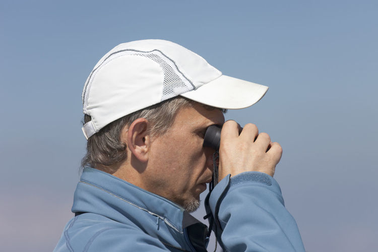 Mature Man looking through binoculars Birdwatching Clear Sky Man Profile Beard Binoculars Blue Sky Cap Casual Clothing Clear Sky Close-up Head Ans Shoulders Headshot Mature Men Men One Man Only One Mature Man Only One Person Outdoors People Real People Side View Sky Stubble Watching