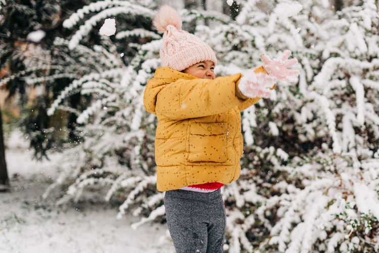 Toddler girl happy with snow day in winter. playing outside on christmas holiday. high quality photo
