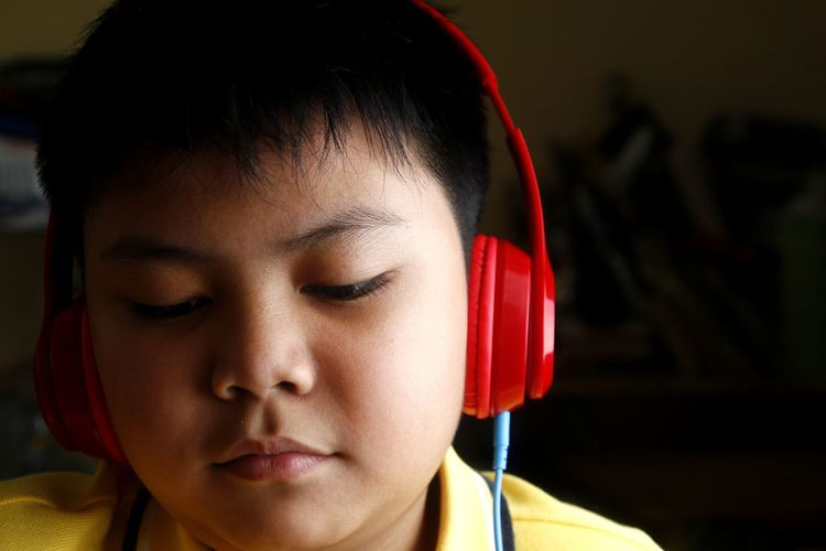 Close-up of boy listening music on headphones against black background