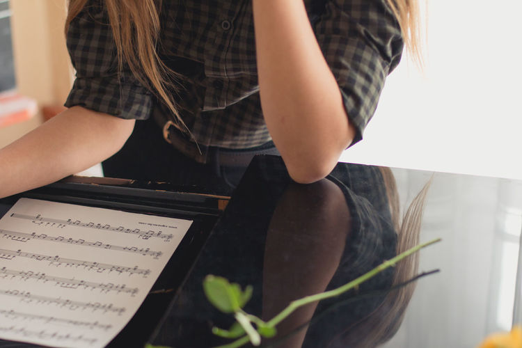 Midsection Of Woman Sitting With Musical Note