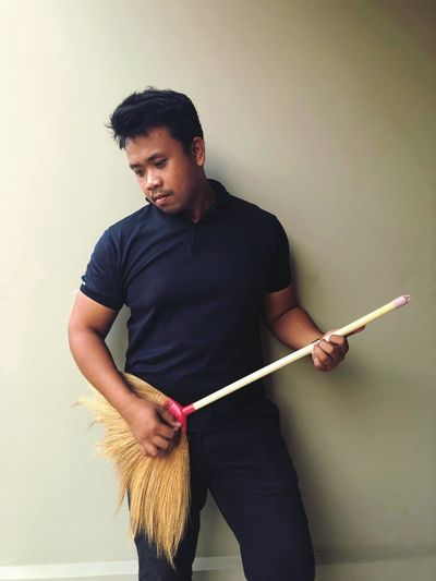 Young man looking away while holding broom against wall