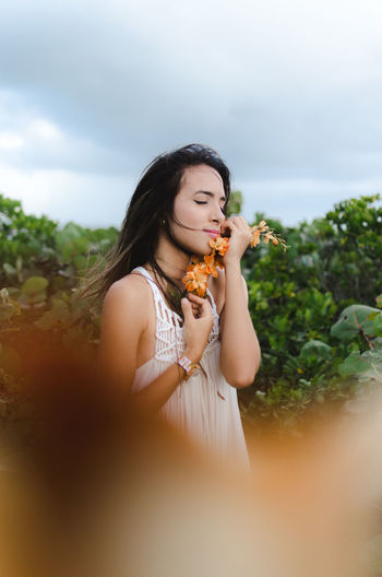 Young woman holding orange flowers against trees against sky