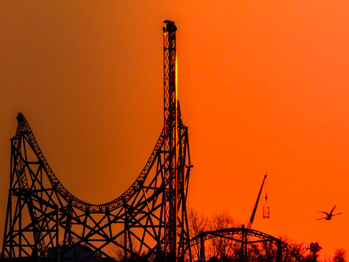 Low Angle View Of Silhouette Rollercoaster Against Orange Sky