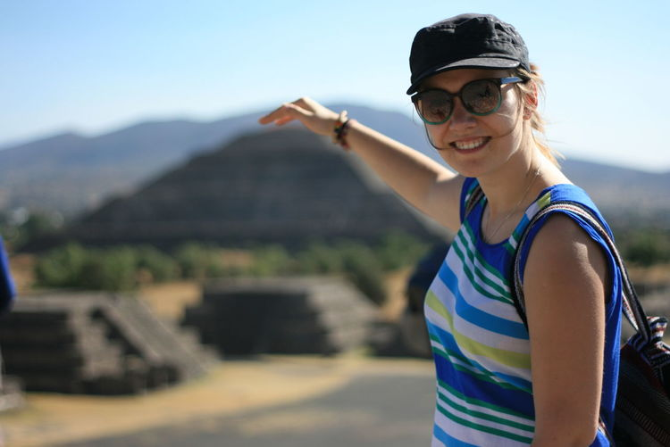 Optical illusion of cheerful woman touching pyramid
