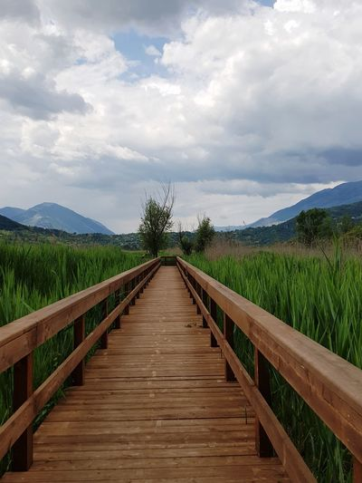 View of wooden boardwalk leading towards mountains against sky