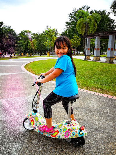 Little Asian girl riding an electric scooter in the park. Little Girl Blue Shirt Long Hair Asian  Asian Girl Cute In The Park Trees Pavement Activity Active Lifestyle  Bangi Family Family❤ Malaysia Truly Asia Selangor Evening Family Time Malaysia Malaysian Park Play Playground Ride Riding Taman Sidewalk Suburb Posing Outdoor Play Equipment