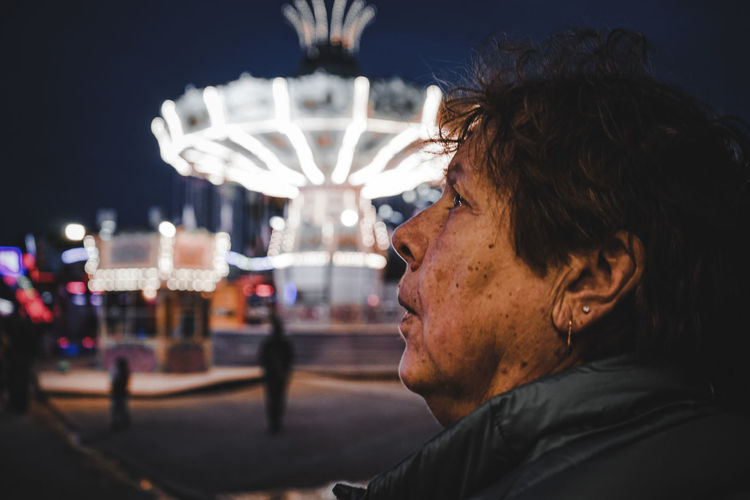Portrait of young man looking at illuminated carousel at night