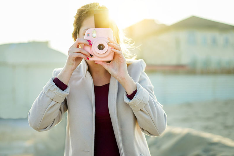 Woman Holding Instant Camera While Standing At Beach
